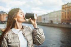 Schöner trinkender Kaffee des jungen Mädchens von einer Papierschale auf dem Hintergrund der alten Stadt Mit Kopienraum f?r Text lizenzfreie stockfotos