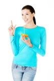 Schöner trinkender Saft der jungen Frau von der Orange. Stockfoto