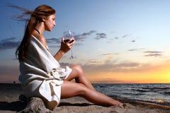 Schöner trinkender Wein der jungen Frau auf Strand Lizenzfreie Stockfotografie