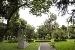 Schöner tropischer Garten mit Bank und Skulptur Stockfotos