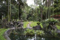 Schöner tropischer Garten mit Teich und Skulptur Stockbild