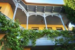Schöner und berühmter bunter hölzerner Balkon Tifliss mit der Weinrebe, die herum wächst stockbilder