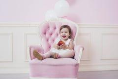 Schöner und glücklicher rosa Innenraum des Babys mit Weinlesestuhl a Stockbild