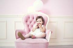 Schöner und glücklicher rosa Innenraum des Babys mit Weinlesestuhl a Stockbilder