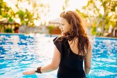 Schöner und Brunette mit der Badebekleidung, die durch das Pool sitzt und Sommer genießt Lizenzfreies Stockfoto