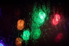 Schöner unscharfer Hintergrund durch das nass Glas stockfoto