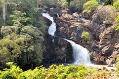 Schöner Wasserfall, der unten in einem tropischen Umgeben kaskadiert Stockbild