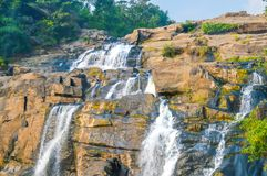 Schöner Wasserfall im tiefen Wald umgeben mit dichtem Waldland und üppigem grünem Wald stockfoto