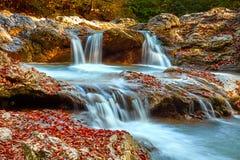 Schöner Wasserfall im Wald bei Sonnenuntergang Herbstlandschaft, gefallene Blätter Stockfoto