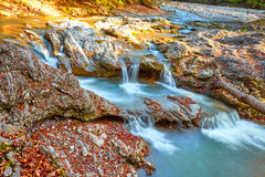 Schöner Wasserfall im Wald bei Sonnenuntergang Herbstlandschaft, gefallene Blätter Lizenzfreie Stockfotografie