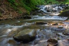 Schöner Wasserfall kommt aus einen enormen Felsen im Wald heraus Stockfotografie