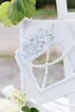 Schöner weißer Rahmen mit Perlen für ein Foto, das an der Treppe hängt Stockfotografie