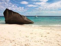 Schöner weißer Sandstrand mit großem Steinschnellboot und blauer Himmel sehen Landschaft Thailand an Stockfotografie