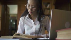 Schöner weiblicher asiatischer Studentenbiologe im Glaslesebuch stock footage