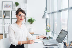 Schöner weiblicher Assistent, der unter Verwendung des Mobiltelefons nennt Junger Büroangestellter, der am Handy hat Geschäft spr lizenzfreies stockfoto