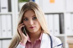 Schöner weiblicher blonder Doktor, der am Telefon spricht Stockbild