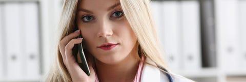 Schöner weiblicher blonder Doktor, der am Telefon spricht Stockfoto