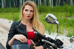 Schöner weiblicher blonder Radfahrer des Porträts auf Motorrad Stockbild