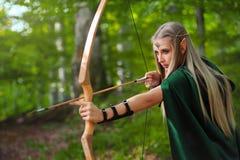 Schöner weiblicher Elfenbogenschütze in der Waldjagd mit einem Bogen Stockbilder