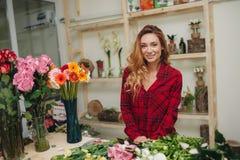 Schöner weiblicher Florist im Blumenladen Stockfotos