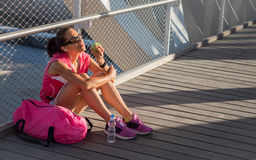 Schöner weiblicher Läufer, der einen Apfel auf einer Brücke stillsteht und isst Lizenzfreie Stockfotografie