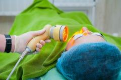 Schöner weiblicher Patient in den Sicherheitsgläsern erhält eine Gesichtshautbehandlung beim im Kosmetikerbüro, Abschluss oben li Lizenzfreie Stockfotos