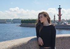 Schöner weiblicher Tourist, der auf die Dammpfeile Vasilyevsky-Insel geht Stockfoto