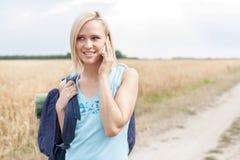 Schöner weiblicher Wanderer, der Handy auf Feld verwendet Stockbilder