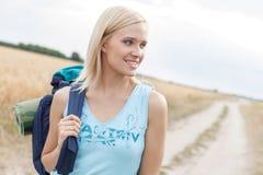 Schöner weiblicher Wanderer mit dem Rucksack, der bei der Stellung auf Feld weg schaut Stockfotografie