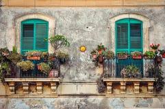 Schöner Weinlesebalkon mit bunten Blumen und Türen lizenzfreies stockfoto