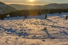 Schöner Wintersonnenaufgang mit Blendenfleck im riesigen Berg Lizenzfreie Stockbilder