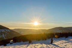 Schöner Wintersonnenaufgang mit Blendenfleck im riesigen Berg Lizenzfreies Stockfoto