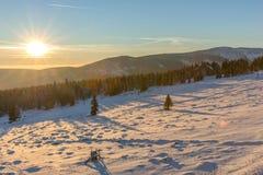 Schöner Wintersonnenaufgang mit Blendenfleck im riesigen Berg Lizenzfreies Stockbild