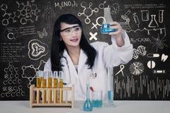 Schöner Wissenschaftler, der Flasche in der Klasse hält Lizenzfreie Stockfotografie