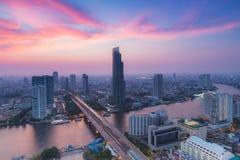 Schöner Wolkenhintergrund, modernes Geschäfts-Gebäude entlang der Flusskurve in Bangkok-Stadt Stockbild