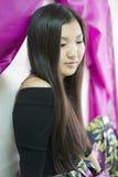 Schöner Yakut das Mädchen, das auf dem Bett sitzt stockfoto