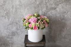 Schöner zarter Blumenstrauß von Blumen im weißen Kasten auf grauem ackground mit Raum für Text Stockbilder