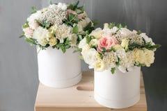 Schöner zarter Blumenstrauß von Blumen im weißen Kasten auf grauem ackground mit Raum für Text Stockbild