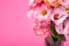 Schöner zarter rosa Eustoma blüht Blumenstrauß im Vase, der auf Rosa lokalisiert wird Stockfotografie