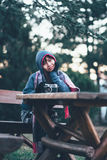 Schönes äußeres Sitzen des jungen Mädchens mit Kamera auf Tabelle Stockbilder