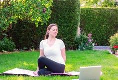 Schönes übendes Yoga der jungen Frau im Garten, der draußen Führer des Online-Tutorials oder Trainer auf Laptop folgt stockfoto