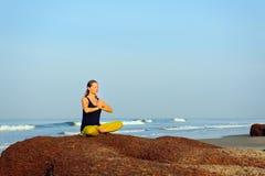 Schönes übendes Yoga der jungen Frau und Übungen am Sommerozeanstrand ausdehnen lizenzfreies stockbild
