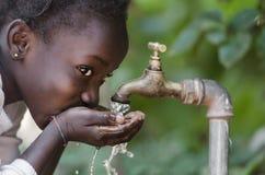 Schönes afrikanisches Kind, das von einem Leitungswasser-Knappheits-Symbol trinkt Lizenzfreies Stockbild
