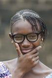 Schönes afrikanisches Mädchen, das draußen mit den Händen auf Kinn denkt Lizenzfreie Stockbilder