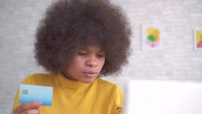 Schönes Afroamerikanermädchen mit einer Afrofrisur mit einer Bankkarte in der Hand und einem Laptop in der modernen Wohnung stock video footage