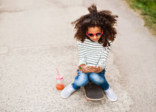 Schönes Afroamerikanermädchen mit Smartphone und Skateboard Lizenzfreie Stockbilder