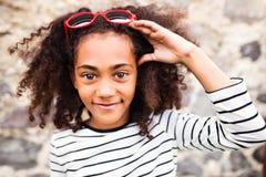 Schönes Afroamerikanermädchen mit Sonnenbrille gegen Stein-wa Lizenzfreie Stockfotografie