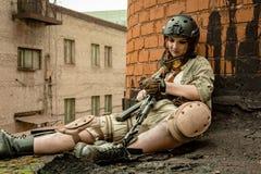 Schönes Armeemädchen mit Gewehr in der Tarnung kleidet in der städtischen Szene und erhält Rest Stockfotografie