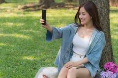 Schönes Asiatinlächeln und Sitzen im Garten, sie selfie durch Smartphone nehmend stockbild