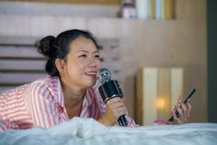 Schönes asiatisches amerikanisches Schlafzimmer-Holdinghandy des Jugendlichmädchen-Gesangkaraokes Lied aufgeregter zu Hause, der  stockfotografie
